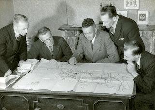 Vijf mannen buigen zich over een grote ontwerptekening op een tafel.
