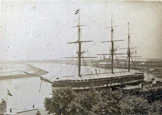 Gezicht op een rivier met op de voorgrond een 19e-eeuwse driemaster met gestreken zeilen.