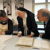 In het restauratieatelier geeft een behoudsmedewerker uitleg over de conservering van een archiefstuk. Twee bezoekers kijken toe.