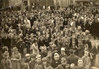 Zwartwitfoto van een grote menigte volwassenen en kinderen, vele met een strik in hun haar.
