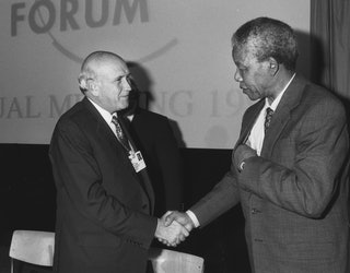 DAVOS/SWITZERLAND, JAN 1992 - South African President F. W. de Klerk shakes hands with Nelson Mandela, South African anti-apartheid leader and head of the ANC at the Annual Meeting of the World Economic Forum in Davos in 1992. Copyright World Economic Forum (http://www.weforum.org)