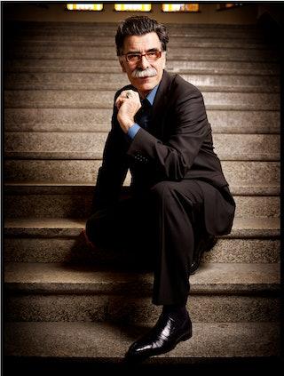 Auteur Kader Abdolah poseert voor de foto, zittend op een trap.