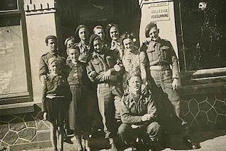 Lachende mensen, burgers en militairen, poseren voor de ingang van een café.