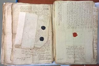 Twee stapels met handgeschreven brieven, sommige voorzien van zegels van zwarte en rode was.