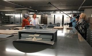 Op de voorgrond ligt een geopende archiefdoos met archiefstukken, links op de achtergrond staan twee vrouwen die door een cameraploeg aan de rechterzijde worden gefilmd.