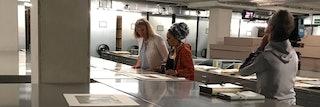 Twee vrouwen bekijken documenten die op stalen kasten ligggen. Rechts van hen staat een cameraman.