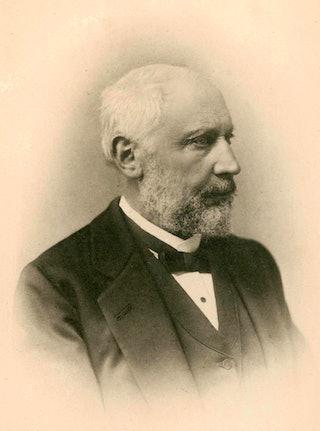 Zwartwitfoto van een man met baard, snor en grijs haar.
