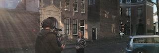 Een cameraman op de rug gezien, staat in een straat, en richt zijn camera op een vrouw.