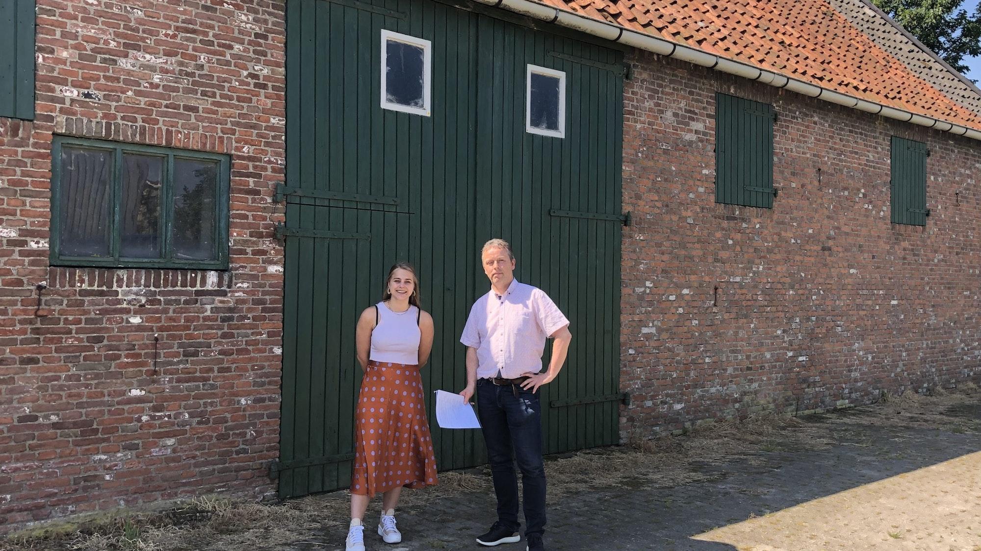 Twee mensen staan voor de deur van een schuur.