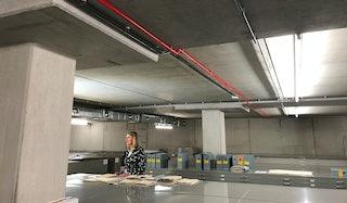 In een depotruimte liggen archiefstukken op een metalen kast. Een vrouw staat erbij en kijkt uit beeld.