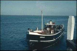 Een veerboot ligt naast een meerpaal. Aan dek zijn mensen.