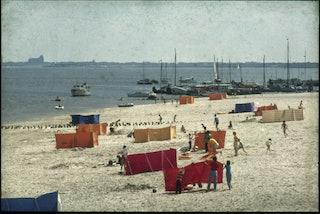 Rode, oranje en gele windschermen staan op een strandje. Op het water liggen jachten afgemeerd. Op de achtergrond is het silhouet van de Grote Kerk van Veere te zien.