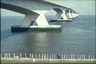 De pijlers van een brug gezien vanaf de wal.