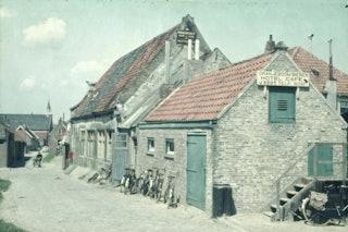 Straat met twee oude vervallen huizen met roodoranje dakpannen.