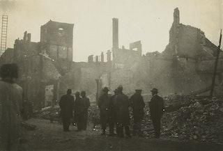 De zwarte silhouetten van een achttal toeschouwers steken af tegen de nasmeulende puinhopen van uitgebrande gebouwen in Middelburg.