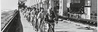Scholieren fietsen achter elkaar aan over de Oosterscheldekering, op de achtergrond een bouwkraan..