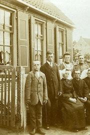 Een gezin poseert voor een huis, sommige familieleden zitten, anderen staan. Iedereen kijkt ernstig.