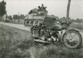 Op de voorgrond een legermotor, op de achtergrond een tank die van de kijker wegrijdt.