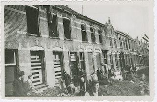 Een rij met woningen waarvan de gevel deels kapotgeschoten is.