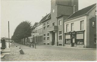 De Westkade (in zuidelijke richting) in Sas van Gent, met in het midden het gemeentehuis Sas van Gent, vóór 1935. Zeeuws Archief, Fotoarchief J. Torbijn, Goes, nr SAS-12.