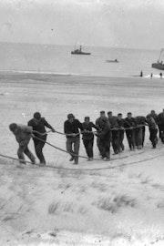Zwart-witfoto van mannen die kabel uit de zee aan land trekken.