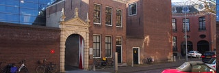 Gevel van de gebouwen van het Zeeuws Archief aan het Hofplein in Middelburg, met de zandstenen toegangspoort naar de ingang.