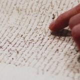 Een geschreven stuk in oud schrift wordt gelezen, een hand die tekst aanwijst in zichtbaar