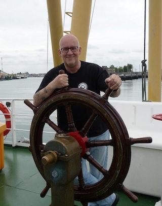 Een glimlachende man staat achter een stuurwiel op het dek van een schip.