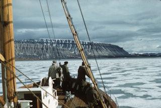 Drie mensen staan op de voorplecht van een boot en kijken uit over water en ijs. Op de achtergrond is een berglandschap.