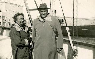Een vrouw en een man staan op het dek van een schip en poseren voor de camera.