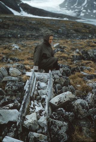Een vrouw met een jas aan staat achter de overblijfselen van kist met beenderen in een bergachtig landschap.