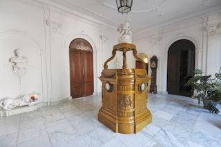 In een grote, witte hal met een marmeren vloer, staat een houten planetarium.