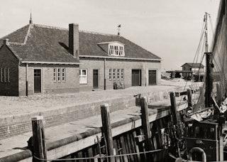 Gezicht vanaf een boot op het gebouw van de vismijn, een laag gebouw met een pannendak.