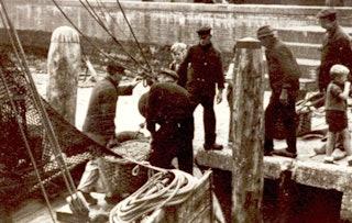 Vanaf de voorplecht van een vissersboot tillen mannen een gevlochten, gesloten mand met vis naar de wal.