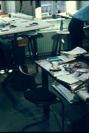 Rommelig kantoor waar twee jongemannen aan tekentafels werken.