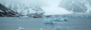 Lichtblauwe ijsschotsen steken her en der uit het water in een bergachtig landschap.