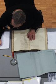 Bovenaanzicht van een man die voorovergebogen aan een tafel zit met om hem heen een uitstalling van archiefstukken.