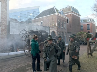 Figuranten in Duitse uniformen lopen voorbij, op de achtergrond is het Zeeuws Archief te zien.