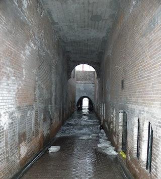 Water loopt de gang tussen de kazematten onder het Keizersbolwerk in op 6 december 2013. Foto Ron van Maanen