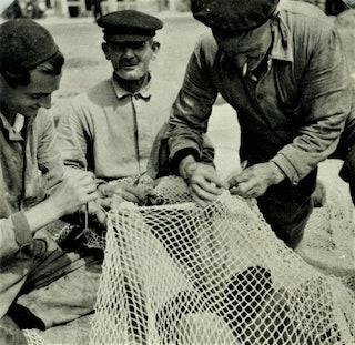 Drie mannen werken aan een visnet.
