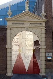 De oude toegangspoort van de voormalige bierbrouwerij De drye Tonnnekens in Middelburg geeft sinds 2000 het publiek toegang tot dé bronnen over het Zeeuwse verleden. In de poort een collage van, v.l.n.r., een doopakte, een kadastrale kaart, een akte van de burgerlijke stand en een portretfoto.