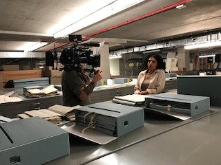Op de voorgrond geopende archiefdozen op stalen archiefkasten en daarachter een cameraman die opnamen maakt van een vrouw.