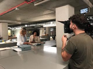 Over de schouder van een cameraman zijn twee vrouwen te zien die zich over enkele documenten buigen.