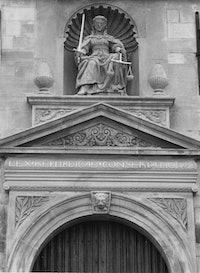 Standbeeld van vrouw justitie in de gevel boven de deur van het stadhuis te Brouwershaven