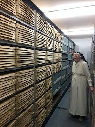 Zuster Mechtild staat in het depot naast een stelling met archieven.